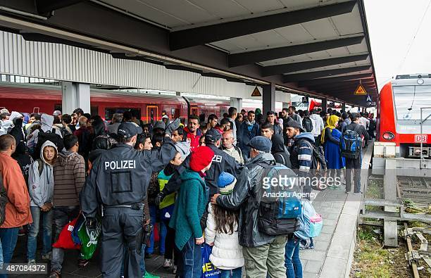 Refugees who travelled by train to the main railway station 'Munich Hauptbahnhof' leave the train under control by police and enter another one to...