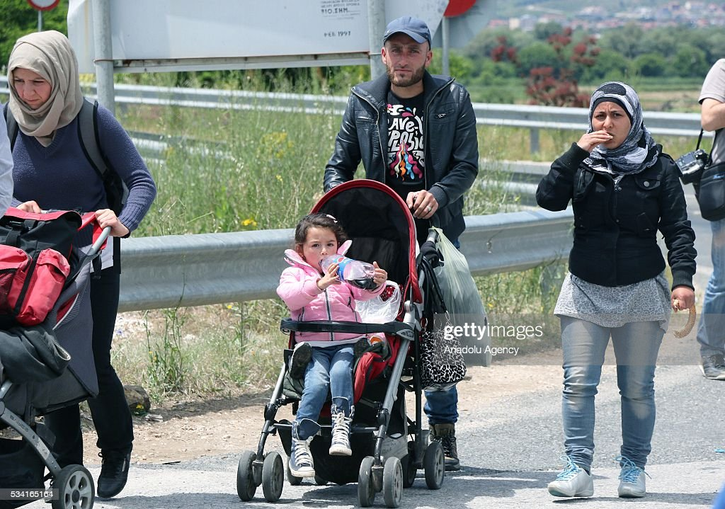 Refugees with their families leave on foot the Idomeni camp along Greek - Macedonian border, as Greek police evacuate the makeshift refugee camp at the Greek-Macedonian border near the northern Greek village of Idomeni on May 25, 2016.