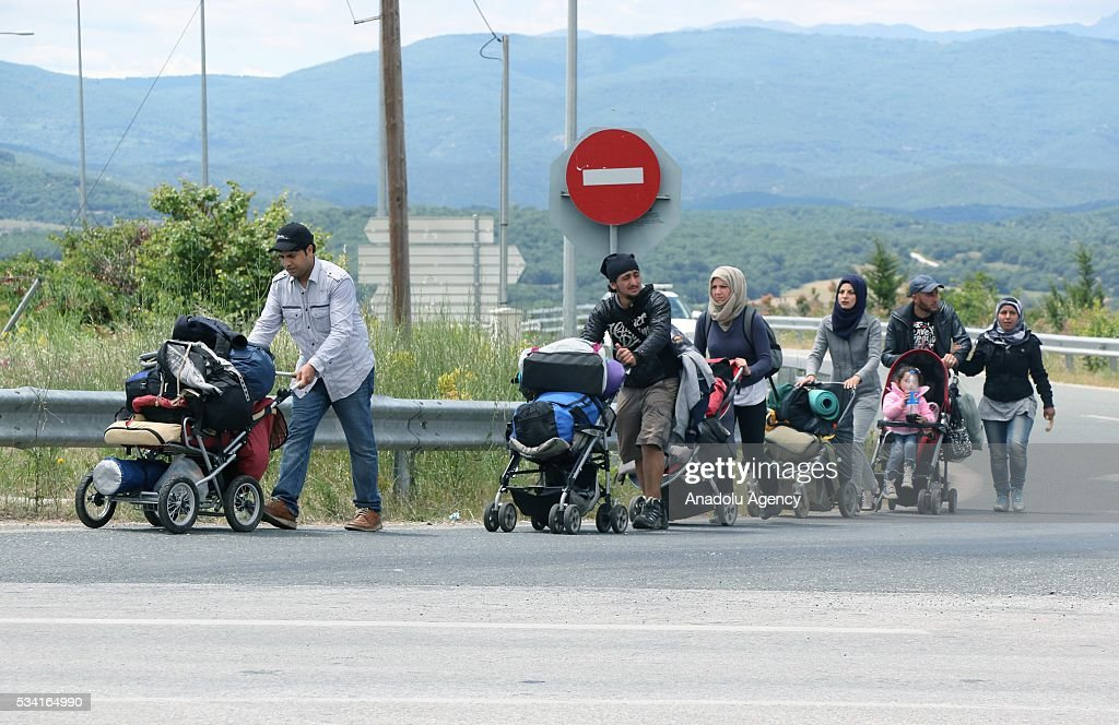 Refugees with their families leave on foot the Idomeni camp, as Greek police evacuate the makeshift refugee camp at the Greek-Macedonian border near the northern Greek village of Idomeni on May 25, 2016.
