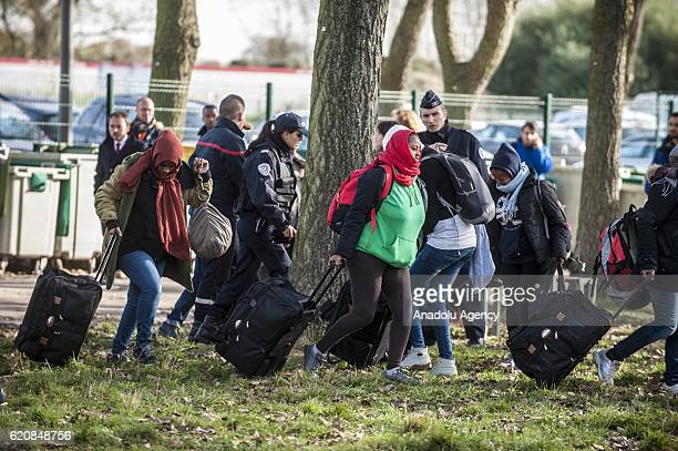 Refugees women surrounded by the staff of the association 'La Vie Active' and police carry their luggages as they walk to climb into a bus...