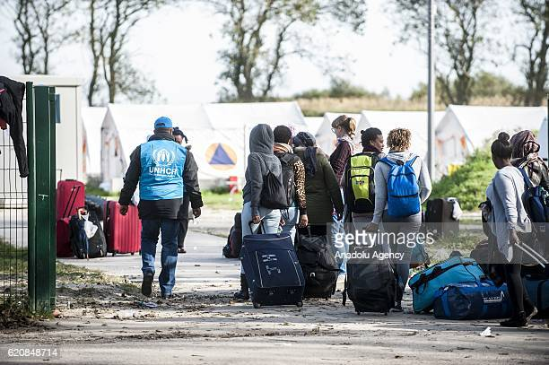 Refugees women surrounded by the staff of the UNHCR and police carry their luggages as they walk to climb into a bus afterleaving the 'Jules Ferry'...