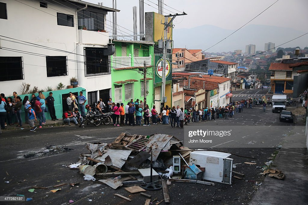 Refuse from a barricade put up by protesters clutters the street in front of a long queue to buy basic foodstuffs at a supermarket before sunrise on March 8, 2014 in San Cristobal, the capital of Tachira state, Venezuela. Shortage of such products as flour, milk and sugar have made life increasingly difficult for residents of Tachira, which has been a focal point for anti-government protests for almost a month.