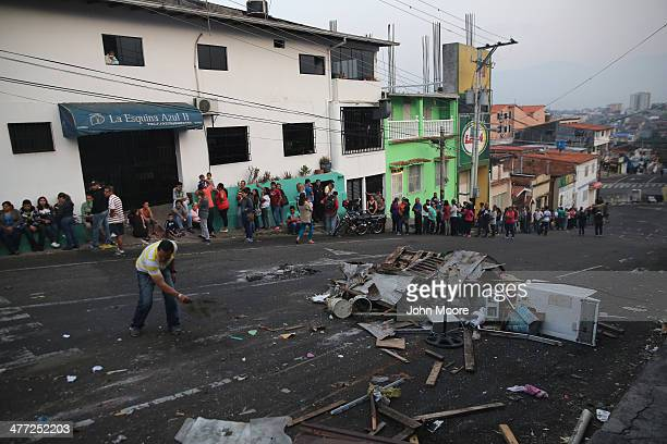 Refuse from a barricade put up by protesters clutters the street in front of a long queue to buy basic foodstuffs at a supermarket on March 8 2014 in...