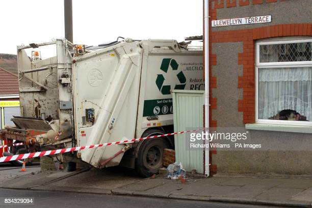 A refuse lorry after it crashed into parked cars and ends up lodged in the side of a house
