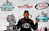 Regan Smith driver of the Fire Alarm Services Chevrolet poses with the Miles the Monster Trophy in Victory Lane after winning the NASCAR XFINITY...