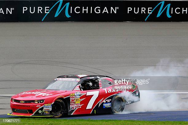 Regan Smith driver of the TaxSlayercom Chevrolet celebrates with a burnout after winning the NASCAR Nationwide Series Alliance Truck Parts 250 at...
