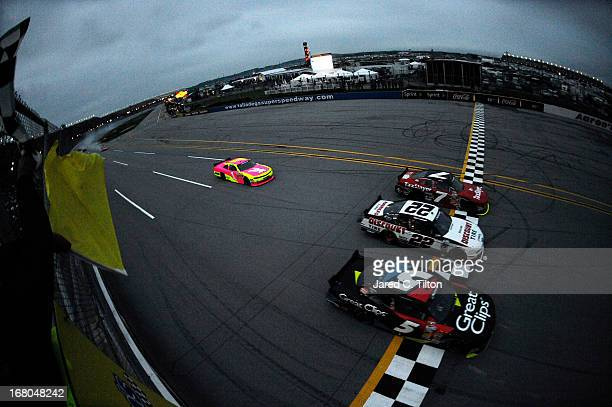 Regan Smith driver of the TaxSlayercom Chevrolet crosses the finish first ahead of Kasey Kahne driver of the Great Clips Chevrolet and Joey Logano...