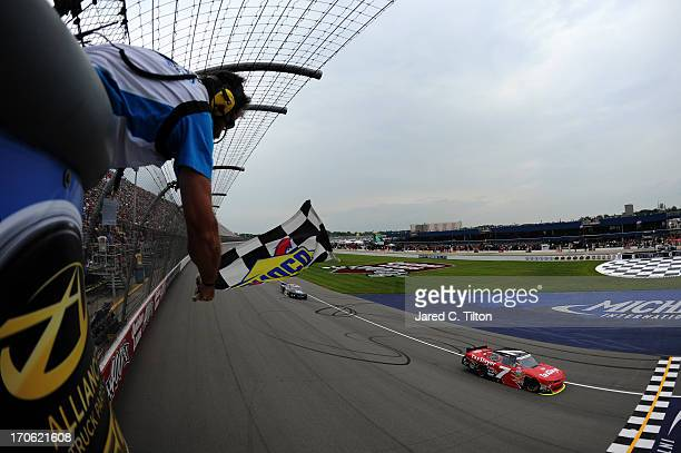 Regan Smith driver of the TaxSlayercom Chevrolet races to the checkerd flag to win the NASCAR Nationwide Series Alliance Truck Parts 250 at Michigan...