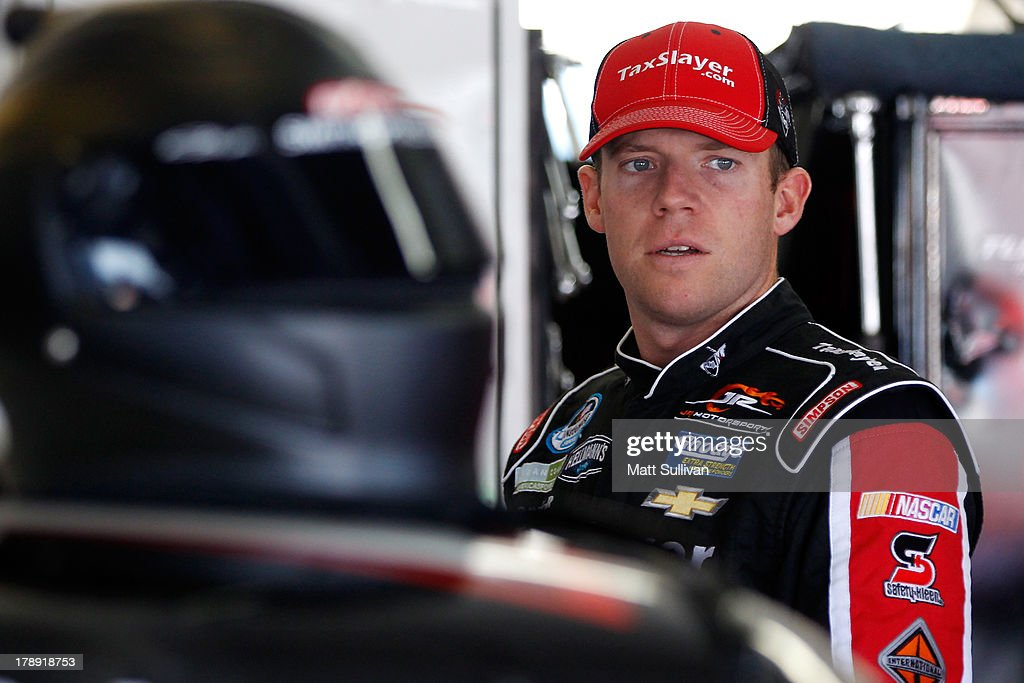 Regan Smith, driver of the #7 TaxSlayer.com Chevrolet, stands in the garage area during practice for the NASCAR Nationwide Series Great Clips/Grit Chips 300 at Atlanta Motor Speedway on August 31, 2013 in Hampton, Georgia.