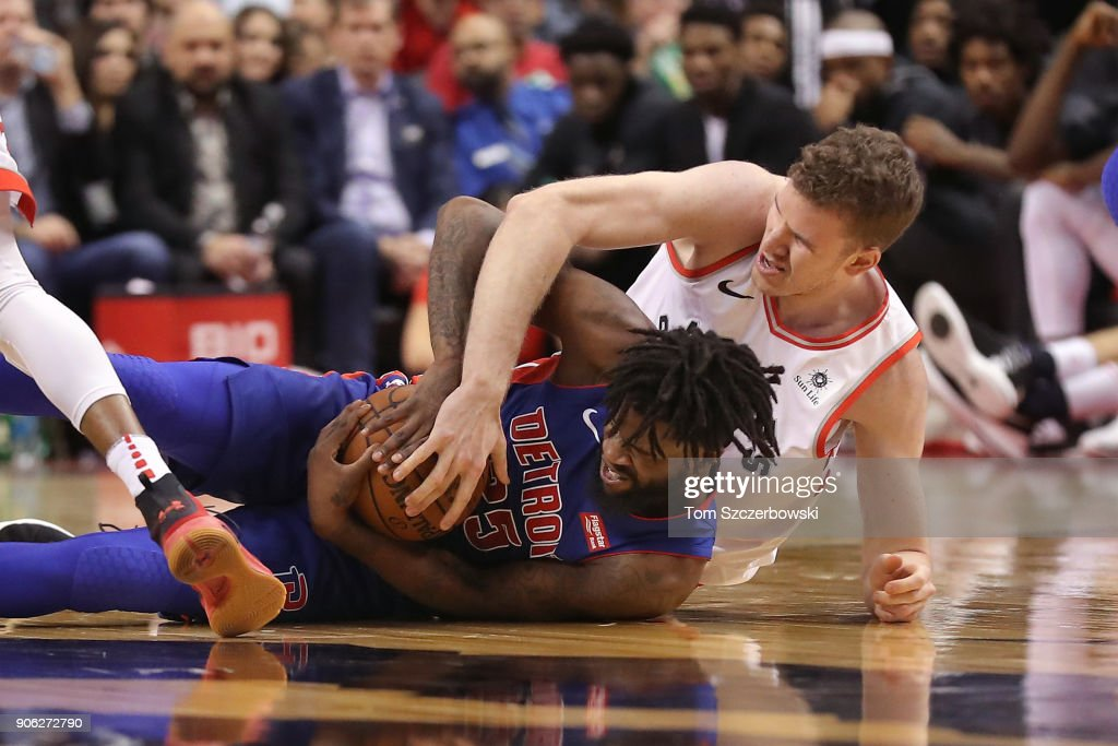 Reggie Bullock #25 of the Detroit Pistons secures a loose ball as Jakob Poeltl #42 of Toronto Raptors battles for the ball at Air Canada Centre on January 17, 2018 in Toronto, Canada.
