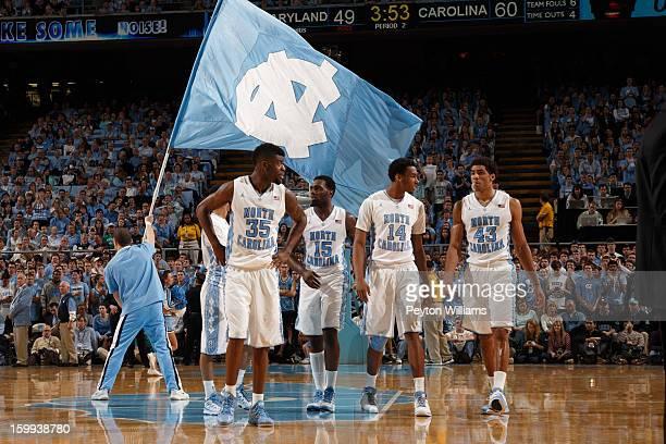 Reggie Bullock PJ Hairston Desmond Hubert and James Michael McAdoo of the North Carolina Tar Heels walk up the court while a cheerleader holds a flag...