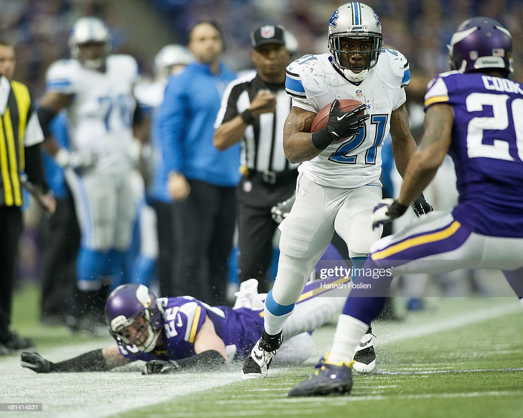 Reggie Bush #21 of the Detroit Lions carries the ball against Chris Cook #20 of the Minnesota Vikings as teammate Chad Greenway #52 looks on after a missed tackle during the game on December 29, 2013 at Mall of America Field at the Hubert H. Humphrey Metrodome in Minneapolis, Minnesota.