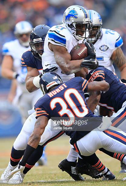 Reggie Bush of the Detroit Lions is tackled by Demontre Hurst of the Chicago Bears Ryan Mundy and Jon Bostic during the second quarter at Soldier...