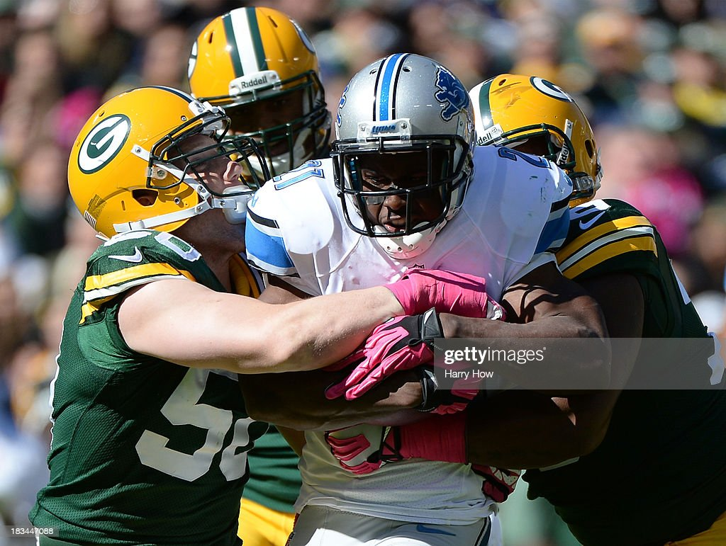 Reggie Bush #21 of the Detroit Lions is wrapped up by A.J. Hawk #50 of the Green Bay Packers during the second quarter at Lambeau Field on October 6, 2013 in Green Bay, Wisconsin.