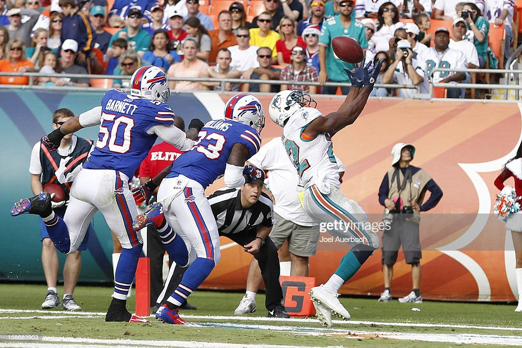 <a gi-track='captionPersonalityLinkClicked' href=/galleries/search?phrase=Reggie+Bush&family=editorial&specificpeople=183392 ng-click='$event.stopPropagation()'>Reggie Bush</a> #22 of the Miami Dolphins catches a 12 yard pass from Ryan Tannehill #17 (not pictured) in front of Aaron Williams #23 of the Buffalo Bills for his third touchdown of the day on December 23, 2012 at Sun Life Stadium in Miami Gardens, Florida. The Dolphins defeated the Bills 24-10.
