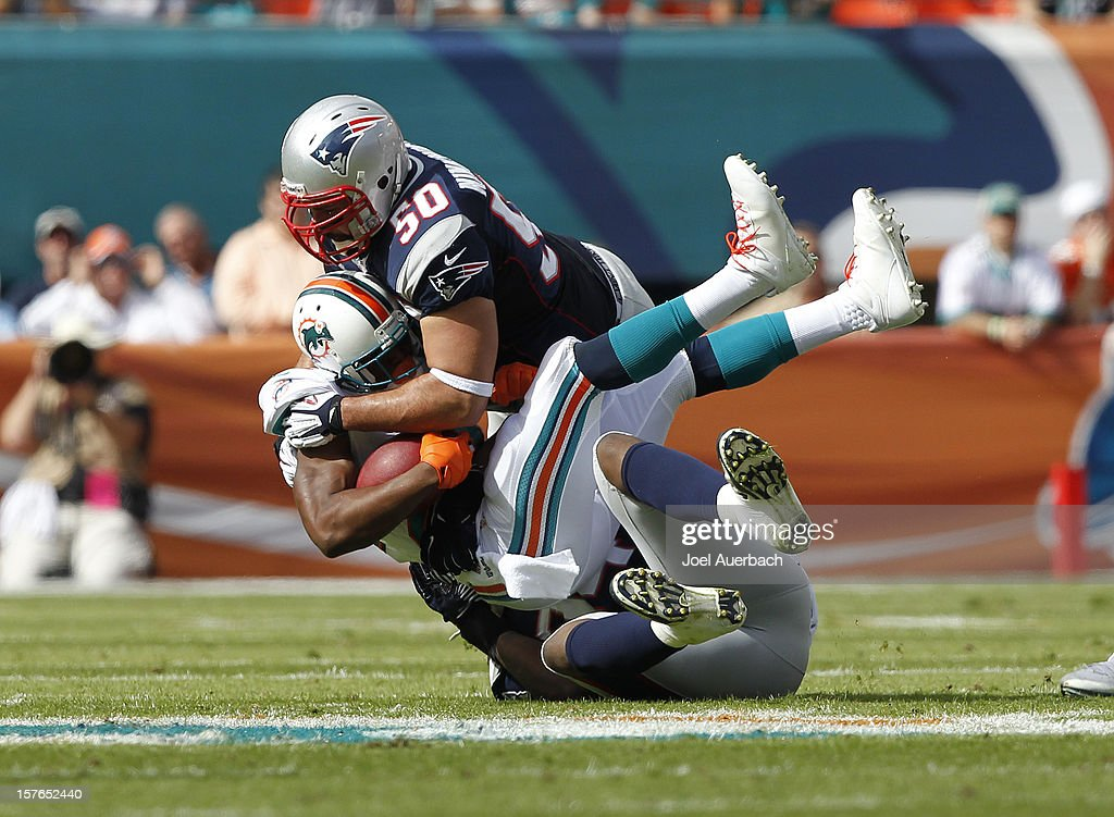 Reggie Bush of the Miami Dolphins is tackled by Rob Ninkovich and Justin Francis of the New England Patriots on December 2 2012 at Sun Life Stadium...