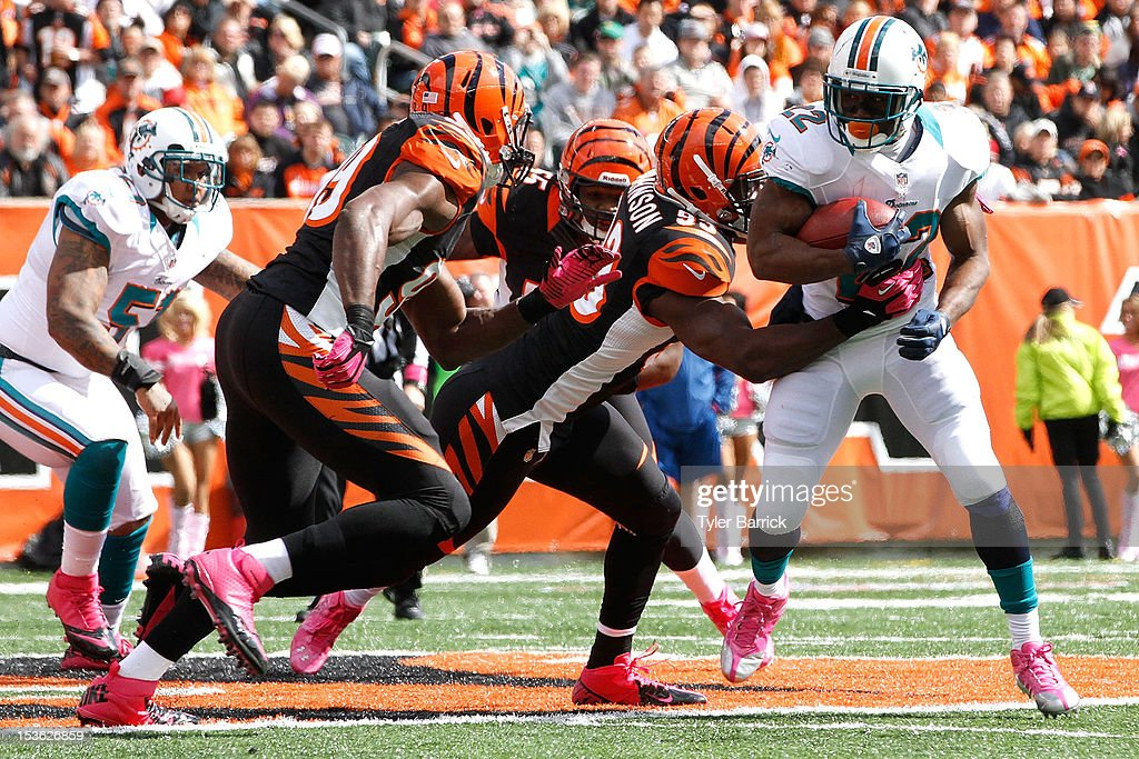 <a gi-track='captionPersonalityLinkClicked' href=/galleries/search?phrase=Reggie+Bush&family=editorial&specificpeople=183392 ng-click='$event.stopPropagation()'>Reggie Bush</a> #22 of the Miami Dolphins, rushes against Wallace Gilberry #95 of the Cincinnati Bengals at Paul Brown Stadium on October 7, 2012 in Cincinnati, Ohio.