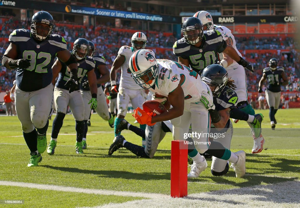 <a gi-track='captionPersonalityLinkClicked' href=/galleries/search?phrase=Reggie+Bush&family=editorial&specificpeople=183392 ng-click='$event.stopPropagation()'>Reggie Bush</a> #22 of the Miami Dolphins rushes for a touchdown during a game against the Seattle Seahawks at Sun Life Stadium on November 25, 2012 in Miami Gardens, Florida.