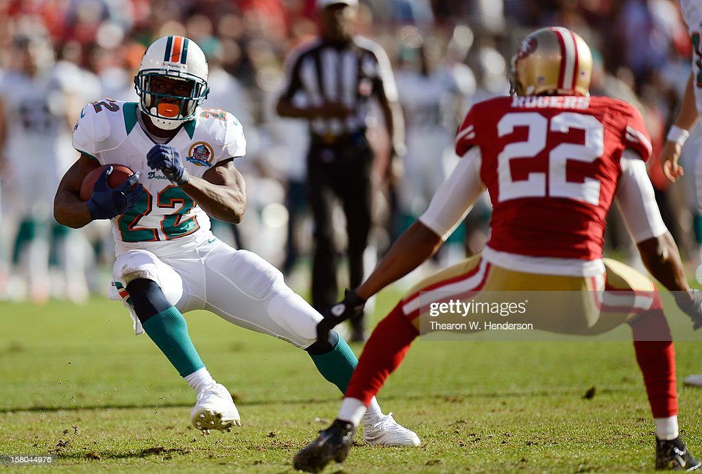 Reggie Bush #22 of the Miami Dolphins rushes with the ball and puts a move on Carlos Rogers #22 of the San Francisco 49ers in the first quarter at Candlestick Park on December 9, 2012 in San Francisco, California. The 49ers won the game 27-13.