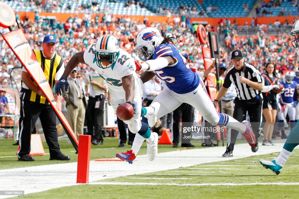 <a gi-track='captionPersonalityLinkClicked' href=/galleries/search?phrase=Reggie+Bush&family=editorial&specificpeople=183392 ng-click='$event.stopPropagation()'>Reggie Bush</a> #22 of the Miami Dolphins scores a touchdown while being defended by Kelvin Sheppard #55 of the Buffalo Bills on December 23, 2012 at Sun Life Stadium in Miami Gardens, Florida.