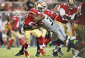 Reggie Bush of the San Francisco 49ers gets tackled by Kam Chancellor of the Seattle Seahawks during an NFL football game at Levi's Stadium on...