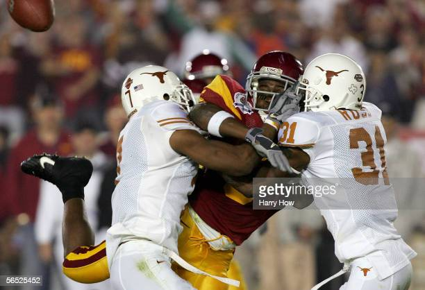 Reggie Bush of the USC Trojans fumbles the ball under pressure from Michael Huff and Aaron Ross of the Texas Longhorns during the second quarter of...