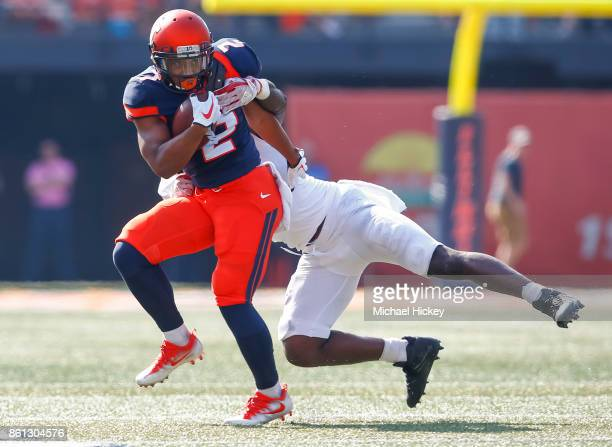 Reggie Corbin of the Illinois Fighting Illini runs the ball as Deonte Roberts of the Rutgers Scarlet Knights makes the tackle at Memorial Stadium on...