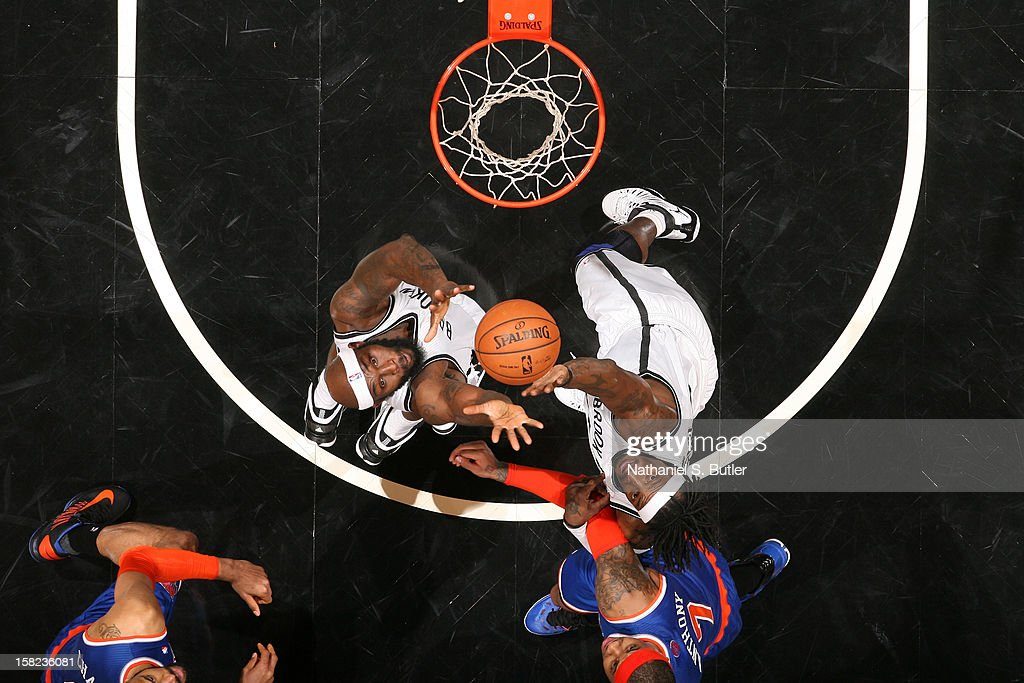Reggie Evans #30 and Gerald Wallace #45 of the Brooklyn Nets rebound against Carmelo Anthony #7 of the New York Knicks on December 11, 2012 at the Barclays Center in the Brooklyn borough of New York City.