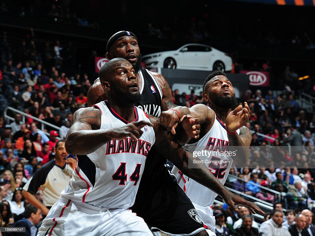 Reggie Evans #30 of the Brooklyn Nets battles for positioning against Ivan Johnson #44 and DeShawn Stevenson #92 of the Atlanta Hawks on January 16, 2013 at Philips Arena in Atlanta, Georgia.