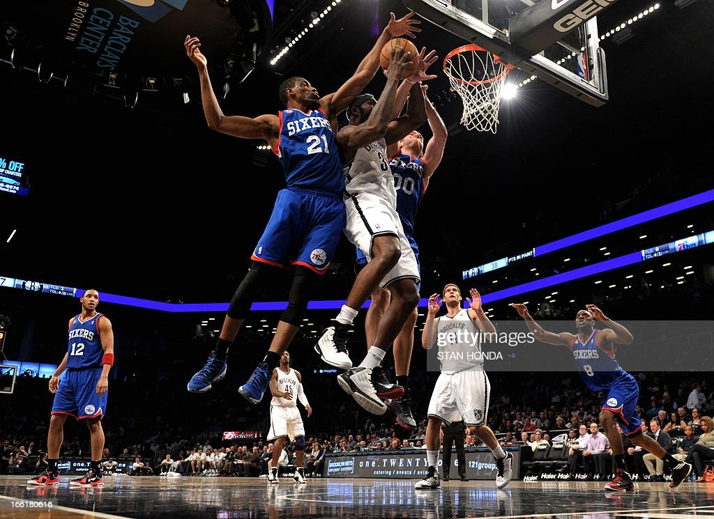 Reggie Evans (C) of the Brooklyn Nets fights for rebound against Thaddeus Young (L) and Spencer Hawes (R) of the Philadelphia 76ers during game at the Barclays Center April 9, 2013 in the Brooklyn borough of New York. The Nets won, 104-83. AFP PHOTO/Stan HONDA