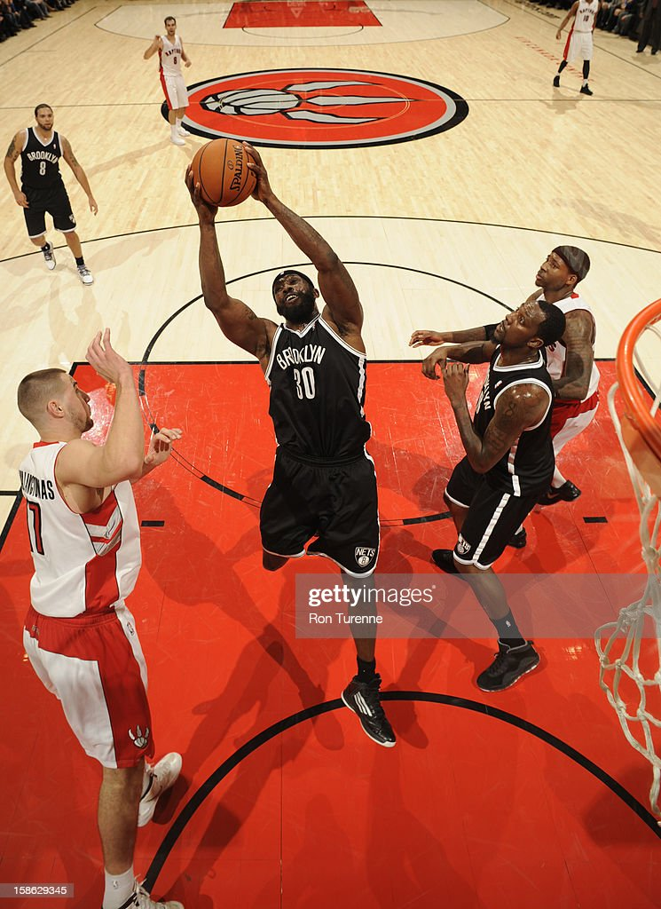 Reggie Evans #30 of the Brooklyn Nets rebounds against Jonas Valanciunas #17 of the Toronto Raptors on December 12, 2012 at the Air Canada Centre in Toronto, Ontario, Canada.