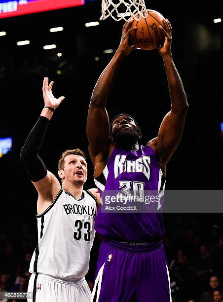 Reggie Evans of the Sacramento Kings attempts a dunk over Mirza Teletovic of the Brooklyn Nets in the first half at the Barclays Center on December...