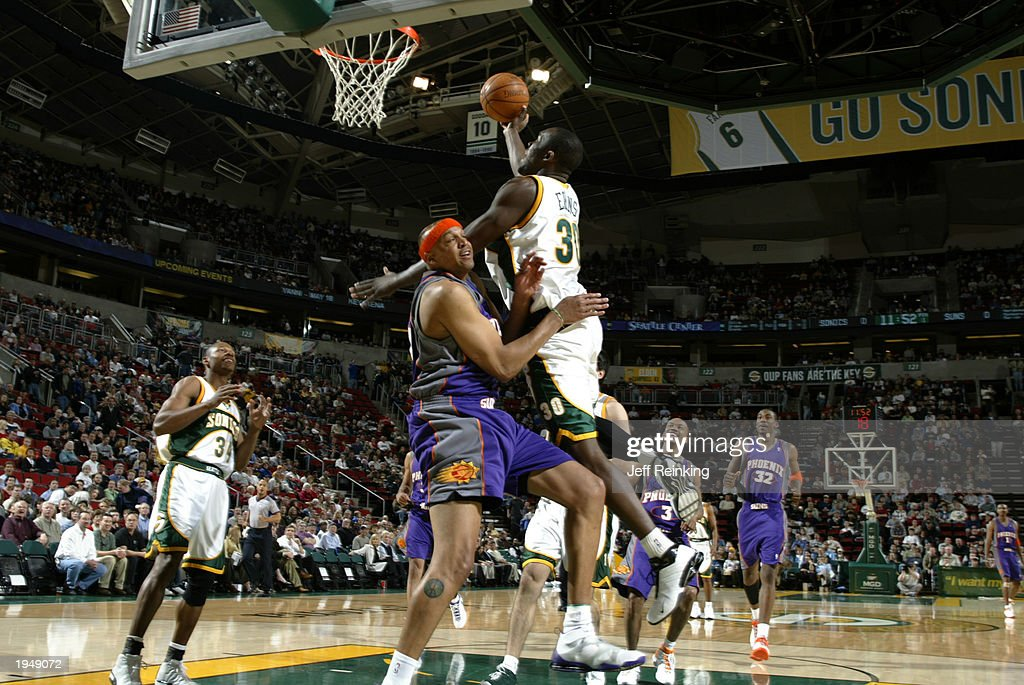Reggie Evans of the Seattle Sonics goes to the basket against Scott Williams of the Phoenix Suns during the game at Key Arena on April 16 2003 in...