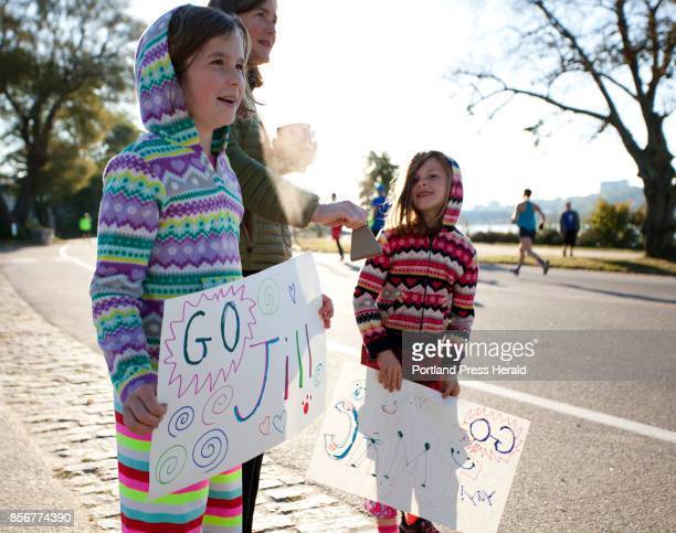 Reggie Hackleman of Portland and her daughters Mary Hackleman left and Melody Hackleman cheer on runners along Baxter Boulevard during the Maine...