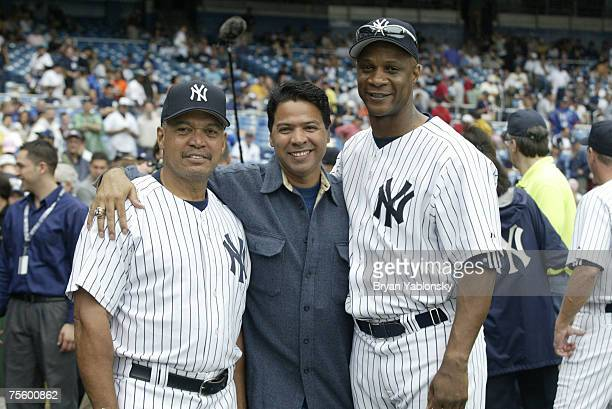 Reggie Jackson and Darryl Strawberry of the New York Yankees huddle around New York Yankee official Ray Negron during old timers celebration day at...