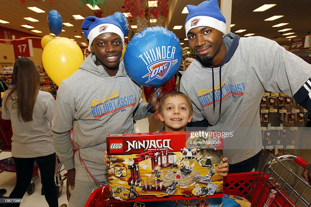 Reggie Jackson (L) and Marcus Dove (R) of the Oklahoma City Thunder shop for toys during a holiday shopping spree with ten families from the Grandparents Raising Grandchildren program on Tuesday, Dec. 13 at a Target store in northwest Oklahoma City in Oklahoma City, Oklahoma.