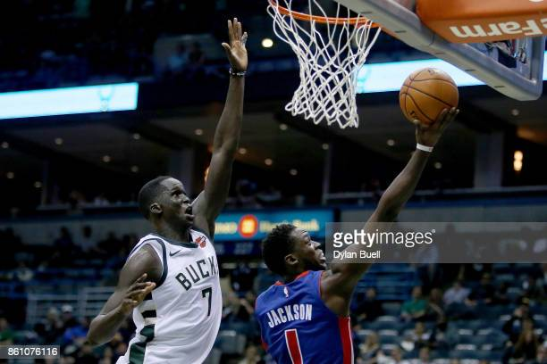 Reggie Jackson of the Detroit Pistons attempts a shot past Thon Maker of the Milwaukee Bucks in the third quarter during a preseason game at BMO...