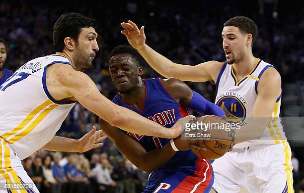Reggie Jackson of the Detroit Pistons is guarded by Zaza Pachulia and Klay Thompson of the Golden State Warriors at ORACLE Arena on January 12 2017...