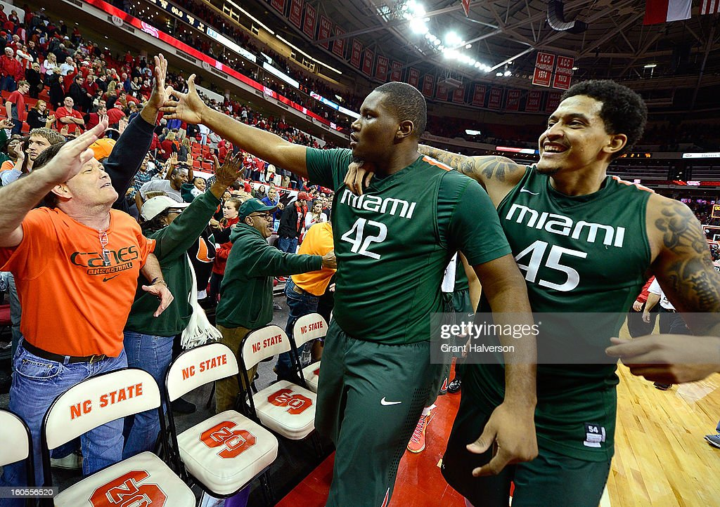 Reggie Johnson #42 and Julian Gamble #45 of the Miami Hurricanes celebrate with fans after a last-second win over the North Carolina State Wolfpack during play at PNC Arena on February 2, 2013 in Raleigh, North Carolina. Miami won 79-78.