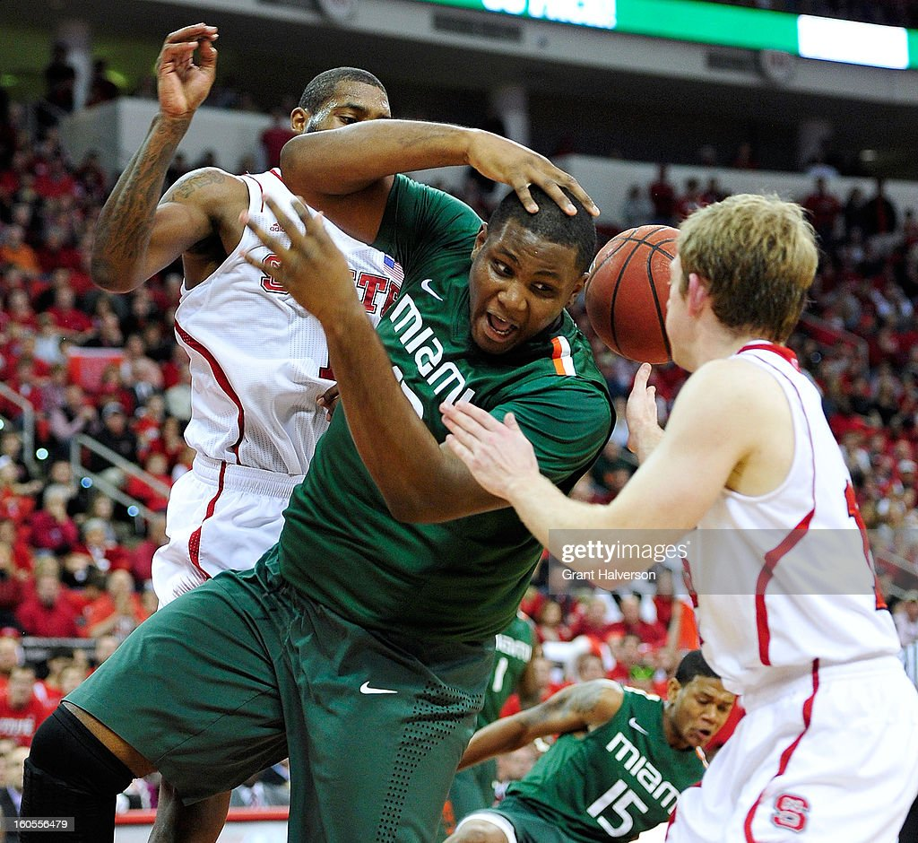 Reggie Johnson #42 of the Miami Hurricanes battles for a rebound with Richard Howell #1 and Tyler Lewis #12 of the North Carolina State Wolfpack during play at PNC Arena on February 2, 2013 in Raleigh, North Carolina. Miami won 79-78.
