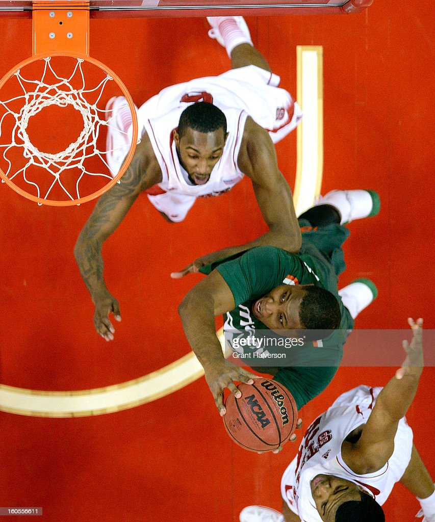 Reggie Johnson #42 of the Miami Hurricanes drives to the basket between C.J. Leslie #5 and T.J. Warren #24 of the North Carolina State Wolfpack during play at PNC Arena on February 2, 2013 in Raleigh, North Carolina. Miami won 79-78.