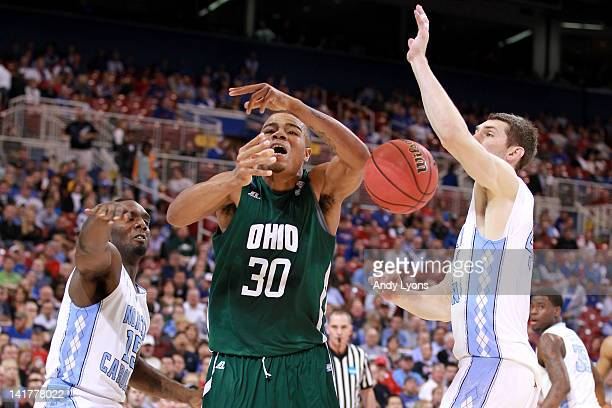 Reggie Keely of the Ohio Bobcats loses the ball as he drives in the first half against PJ Hairston and Tyler Zeller of the North Carolina Tar Heels...