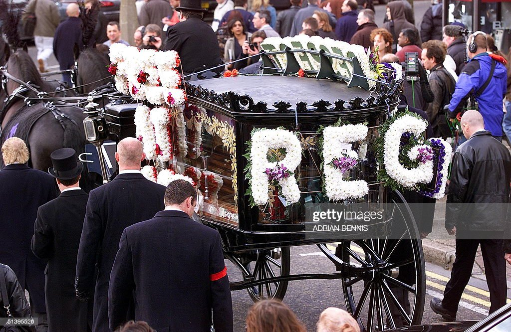 Reggie Kray's horse-drawn hearse drives through East London while people line the streets along the route to St. Matthew's Church in Bethnal Green 11 October 2000. Kray, who died of cancer 10 days ago, was one of Britain's most feared gangsters who held a mafia-like grip on London's East End during the 1960's. Reggie Kray and his twin brother Ronnie were convicted of murder and sentenced to life in prison in 1969.