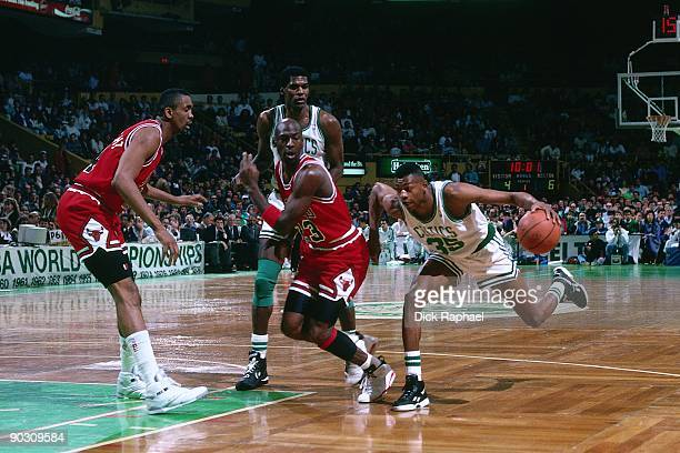 Reggie Lewis of the Boston Celtics drives to the basket against Michael Jordan of the Chicago Bulls during a game played in 1991 at the Boston Garden...