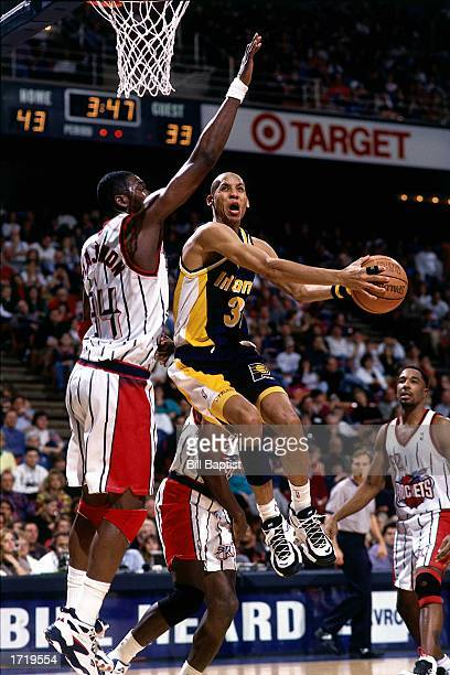 Reggie Miller of the Indiana Pacers drives to the basket against Hakeem Olajuwon of the Houston Rockets during the NBA game at the Summit in 1996 in...