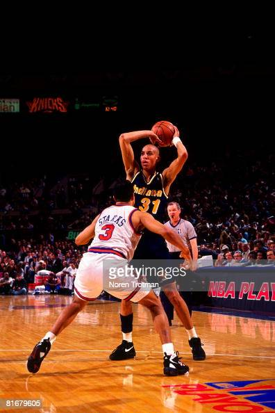 Reggie Miller of the Indiana Pacers looks to pass against John Starks of the New York Knicks in Game One of the Eastern Conference Semifinals during...