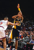 Reggie Miller of the Indiana Pacers passes the ball over the top of John Starks of the New York Knicks during an NBA basketball game circa 1991 at...