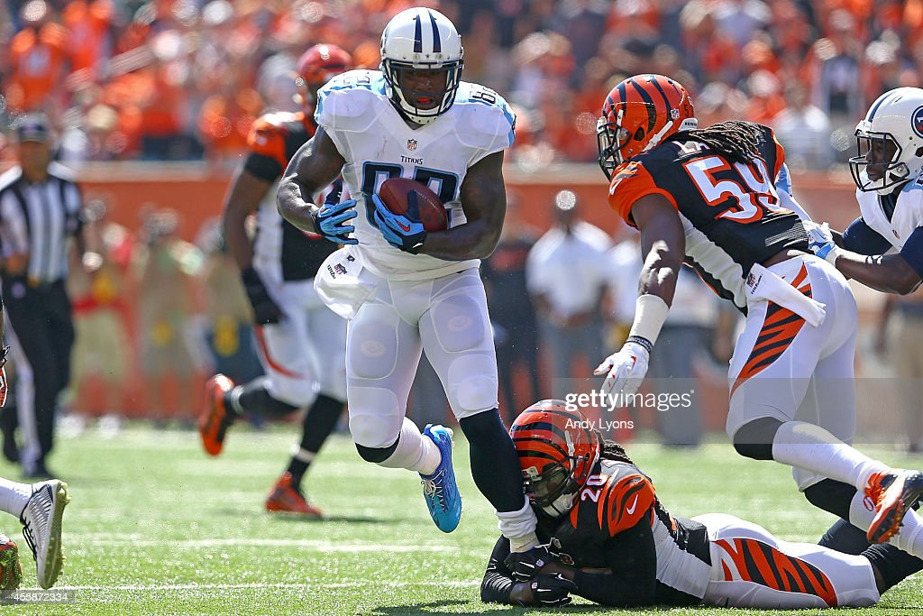 Reggie Nelson of the Cincinnati Bengals grabs the feet of Delanie Walker of the Tennessee Titans as Emmanuel Lamur of the Cincinnati Bengals comes in...