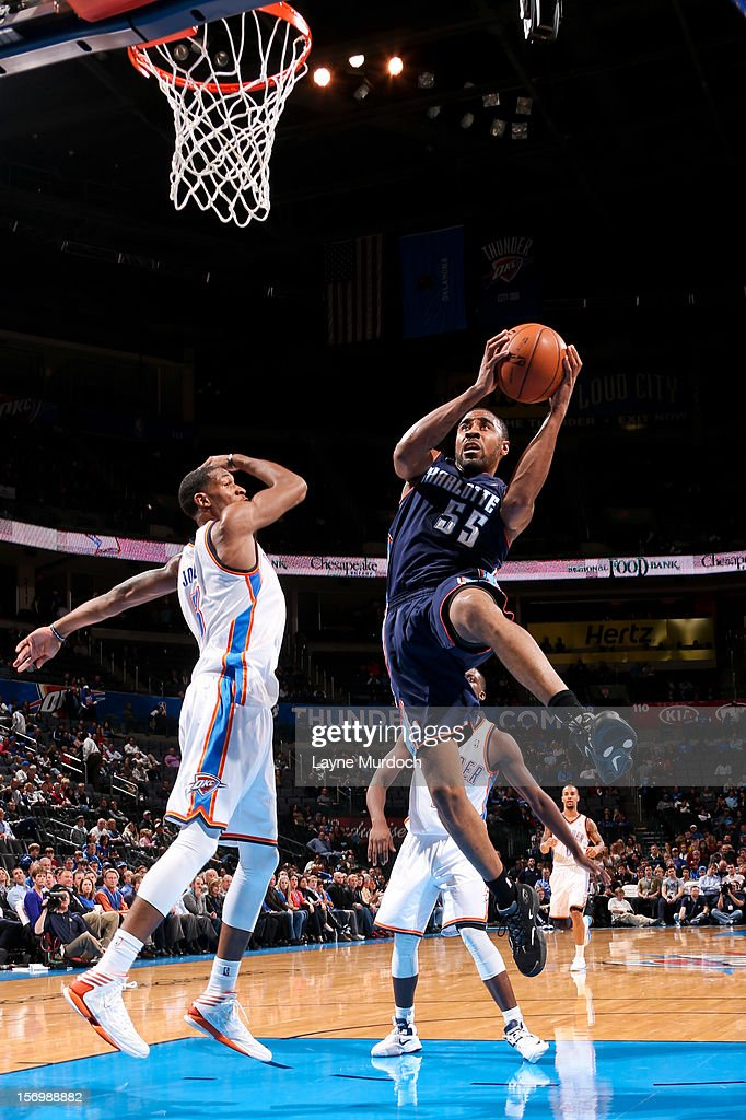 Reggie Williams #55 of the Charlotte Bobcats drives to the basket against <a gi-track='captionPersonalityLinkClicked' href=/galleries/search?phrase=Perry+Jones+-+Jogador+de+basquetebol&family=editorial&specificpeople=9866246 ng-click='$event.stopPropagation()'>Perry Jones</a> III #3 of the Oklahoma City Thunder on November 26, 2012 at the Chesapeake Energy Arena in Oklahoma City, Oklahoma.