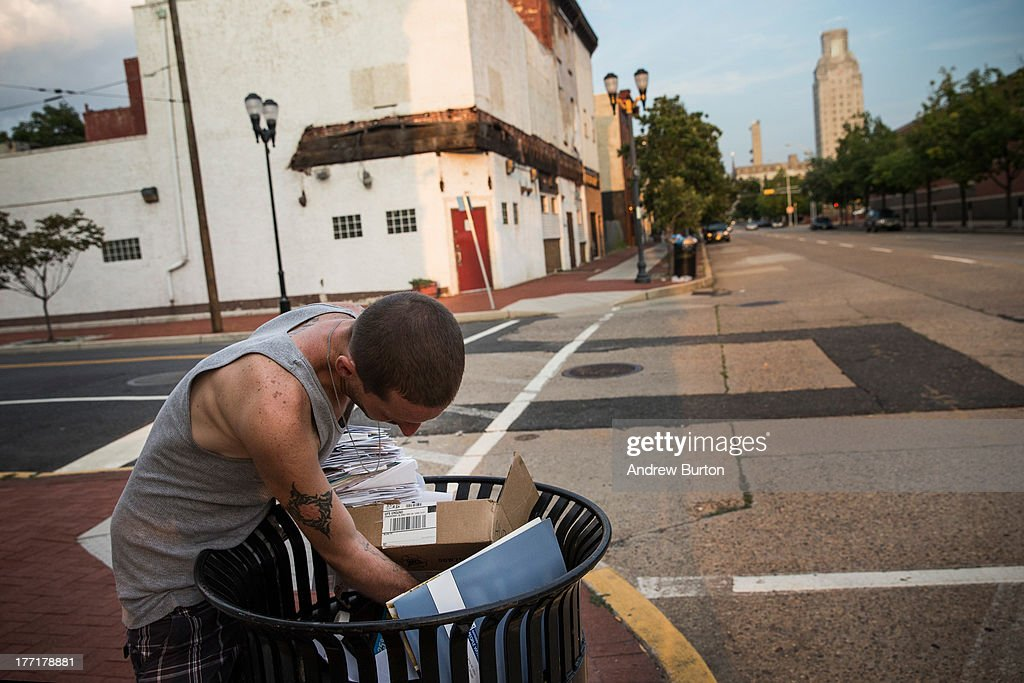 Reggy Colby, age 30 and a recovering heroin addict, digs through the trash looking for food, on August 21, 2013 in Camden, New Jersey. Colby says he got out of jail two days ago, where he was forced to get clean while serving a 30 day sentence. According to Colby, he was in jail for for stealing food after getting hungry. Colby says he grew up in a 'Leave it to Beaver' home in Cherry Hill, an afluent city nearby, and originally went to college for architecture before dropping out. After leaving school he moved to Florida, where he got married and had a daughter, Colby says. He joined the army in 2007, trained as a field artilery specialist and served in Afghanistan in 2009 through 2010, until he was injured in an improvized explosive device, which peppered his body with shrapnel, Colby says. It was while recovering from his injuries that he became addicted to heroin, a drug he had also tried as a teen. Since becoming addicted, he has been dishonorably discharged from the Army, divorced and estranged from his daughter, and has become homeless in Camden. 'As a kid I was terrified to come to Camden. I was so scared - I never thought I would be out here, never....it's just like, what the fuck happened,' Colby says.